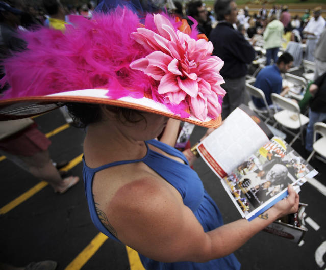 Lisa Scotti, of Baltimore, reads hhere program before the sixth race at Pimlico Race Course, Saturday, May 18, 2013, in Baltimore. The 138th Preakness Stakes horse race takes place Saturday. (AP Photo/Mike Stewart)