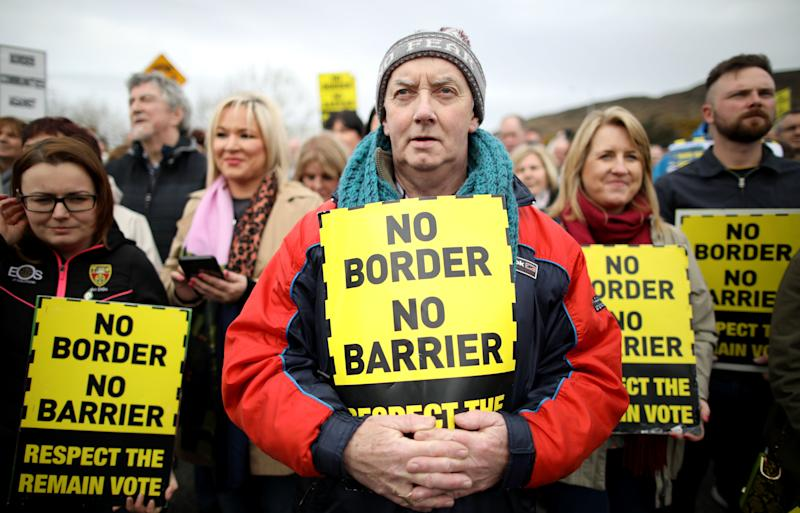 Protesters against any border between Ireland and Northern Ireland because of Brexit hold placards at the Carrickcarnan border between Newry in Norther Ireland and Dundalk in the Irish Republic on March 30, 2019. - British Prime Minister Theresa May on Saturday mulled a possible fourth attempt to get her Brexit agreement through parliament, faced with the growing risk of a chaotic no-deal exit in less than two weeks' time. Britain's exit from the European Union brings with it the fear of the possible reimposition of physical checks on the Irish border, which would be the UK's only land border with the EU, a fear especially real in a no-deal scenario. A so-called hard border could threaten the 1998 Good Friday Agreement that brought an end to decades of civil strife between Protestant supporters of British rule over the province, and Irish Catholic nationalists, who believe in a united Ireland. (Photo by Paul FAITH / AFP) (Photo credit should read PAUL FAITH/AFP/Getty Images)