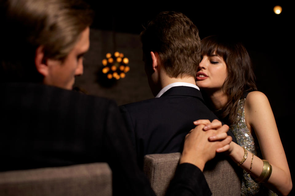 shot from behind of young people at a dinner party with a young woman whispering into the ear of her partner while holding another man's hand behind her partner's back