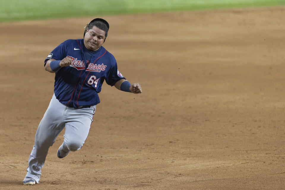 Minnesota Twins' Willians Astudillo rounds third base before scoring a run on a triple by Luis Arraez during the tenth inning of a baseball game against the Texas Rangers in Arlington, Texas, Friday, June 18, 2021. (AP Photo/Andy Jacobsohn)