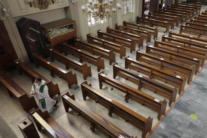 """Catholic priest Fr. Ian Espartero walks past empty pews as he prepares to distribute communion to a few parishioners as a measure to prevent the spread of COVID19 at the Our Lady of Consolation Parish on Sunday, Aug. 2, 2020, in Quezon city, Philippines. Coronavirus infections in the Philippines continues to surge Sunday as medical groups declared the country was waging """"a losing battle"""" against the contagion and asked the president to reimpose a lockdown in the capital. (AP Photo/Aaron Favila)"""