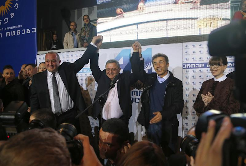 Georgia's Prime Minister Bidzina Ivanishvili, right, parliament speaker David Usupashvili, center, and presidential candidate Giorgi Margvelashvili, left, greet supporters at the Georgian Dream coalition's headquarters in Tbilisi, Georgia, Sunday, Oct. 27, 2013. Giorgi Margvelashvili, a former university rector with limited political experience, should get about 67 percent of the vote, the exit polls predicted. (AP Photo/Sergei Grits)