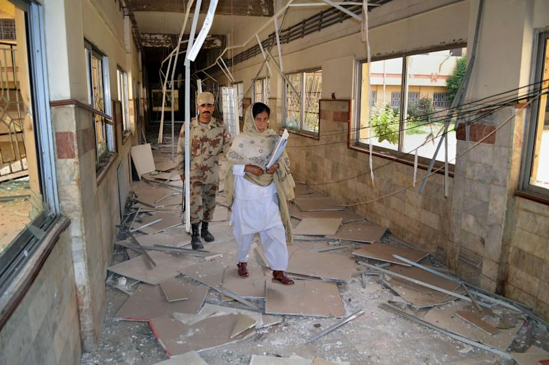 A Pakistani paramilitary soldier and a nurse walk through a damaged corridor caused by Saturday's bombing at the Bolan Medical complex in Quetta, Pakistan, Sunday, June 16, 2013. The radical Lashkar-e-Jhangvi group claimed responsibility for the attacks on the hospital and a women's university bus. (AP Photo/Arshad Butt)