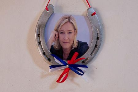 A horseshoe with a photograph of Marine Le Pen, French National Front (FN) political party leader and candidate for French 2017 presidential election, is seen on a wall at her local headquarters in Henin-Beaumont, France, April 6, 2017.  REUTERS/Pascal Rossignol