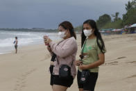 Women wear masks as a precaution against the virus outbreak as they visit a tourism site of Kuta beach, Bali, Indonesia Wednesday, Oct. 6, 2021. Indonesia plans to reopen the airport in the resort island of Bali for international flights on Oct. 14, after closing it for more than a year because of the COVID-19 pandemic. (AP Photo/Firdia Lisnawati)