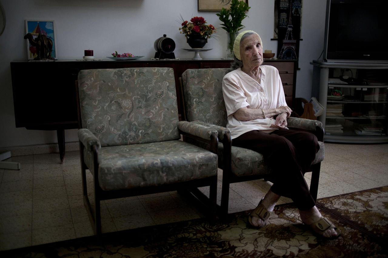 In this photo take on Sunday, May 5, 2013, Holocaust survivor Rivka Fringeru, 82, sits in her living room in Rehovot, central Israel. With a hand on her chest and moistness building in her eyes, Fringeru battled back tears as she reeled off a list of names she has rarely voiced in the past 70 years. First her father, Moshe, then her mother, Hava, and finally her two older brothers, Michael and Yisrael. All perished in the Holocaust after the Harabju family from Dorohoi, Romania was rounded up in 1944 and sent to ghettos and camps. Only Rivka and her brother Marco survived, and like so many others they spent the rest of their lives trying to move on and forget. Now, Yad Vashem, Israel's national Holocaust memorial and museum, is asking them to remember. (AP Photo/Ariel Schalit)