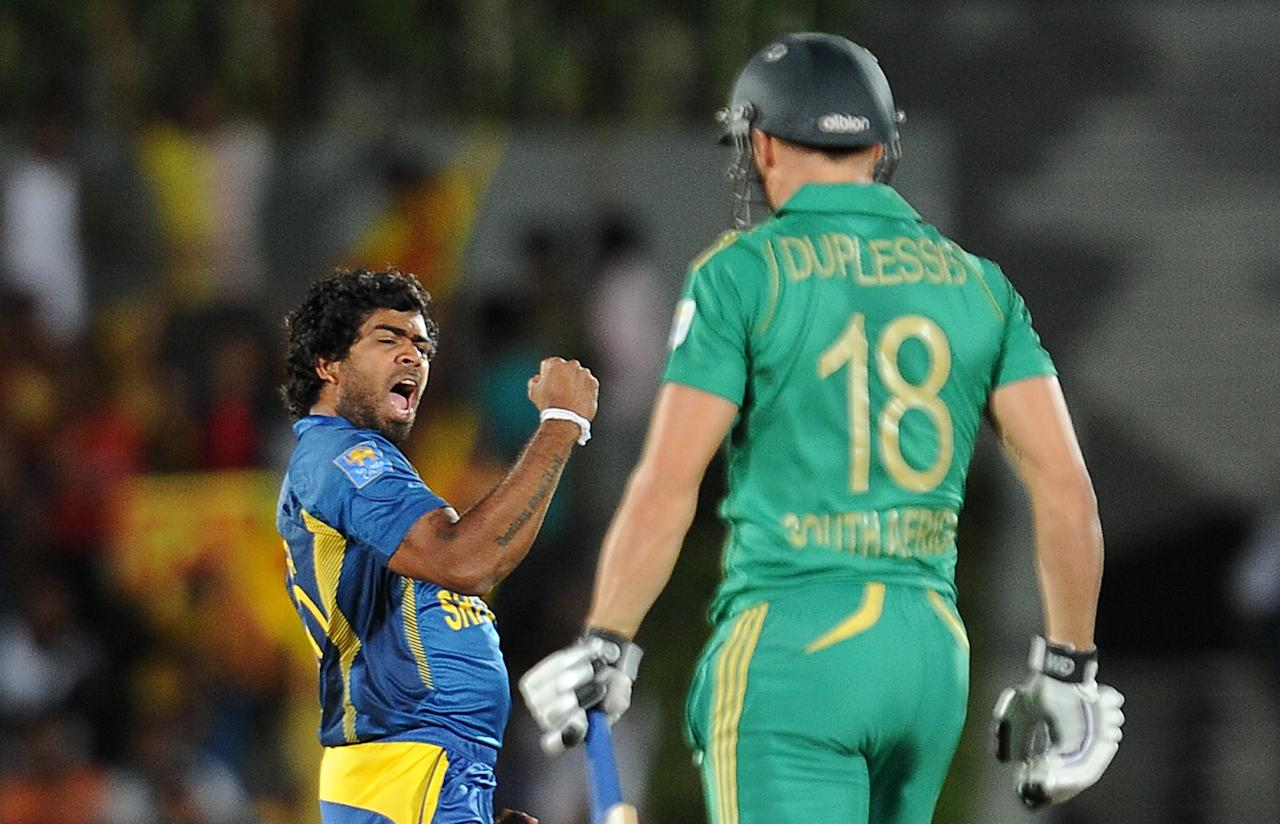 Sri Lankan cricketer Lasith Malinga (L) celebrates after he dismissed South African cricket captain Faf du Plessis (R) during the second Twenty20 cricket match between Sri Lanka and South Africa at the Suriyawewa Mahinda Rajapakse International Cricket Stadium in the southern district of Hambantota on August 4,2013. AFP PHOTO / LAKRUWAN WANNIARACHCHI