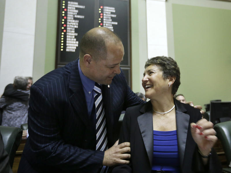 Rhode Island state Sen. Juan Pichardo, D-Providence, congratulates R.I. state Sen. Donna Nesselbush, D-Pawtucket, right,  moments after the R.I. Senate passed a same-sex marriage bill at the Statehouse, in Providence, R.I., Wednesday, April 24, 2013. Nesselbush was the main sponsor of the bill in the Senate. (AP Photo/Steven Senne)