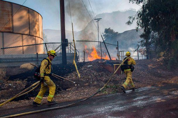 PHOTO: Firefighters run to battle flames from the Maria Fire next to a oil tank at South Mountain Road, in Santa Paula, Ventura County, in California on Nov. 01, 2019. (Apu Gomes/AFP via Getty Images)