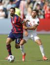 U.S. midfielder Sebastian Lletget (17) is held back by Canada midfielder Jonathan Osorio (21) during the second half of a CONCACAF Gold Cup soccer match in Kansas City, Kan., Sunday, July 18, 2021. (AP Photo/Colin E. Braley)