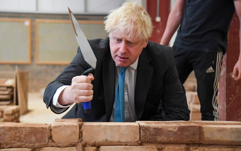 Boris Johnson attempting to lay bricks whilst talking with students during his visit to Exeter College.  - AFP
