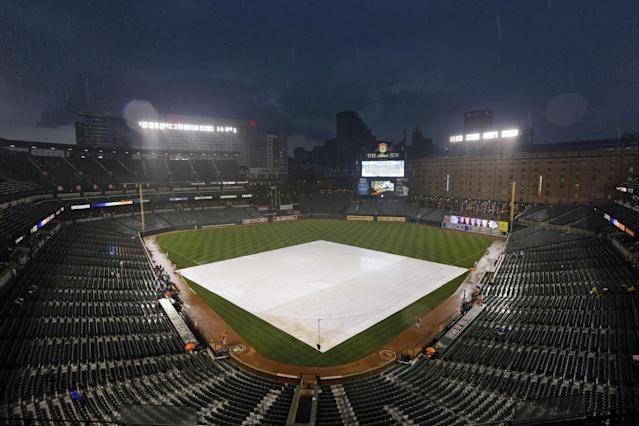 A tarp covers the infield as rain falls before a baseball game between the New York Yankees and Baltimore Orioles, Thursday, Sept. 12, 2013, in Baltimore. The start of the game was delayed on account of the rain. (AP Photo/Patrick Semansky)