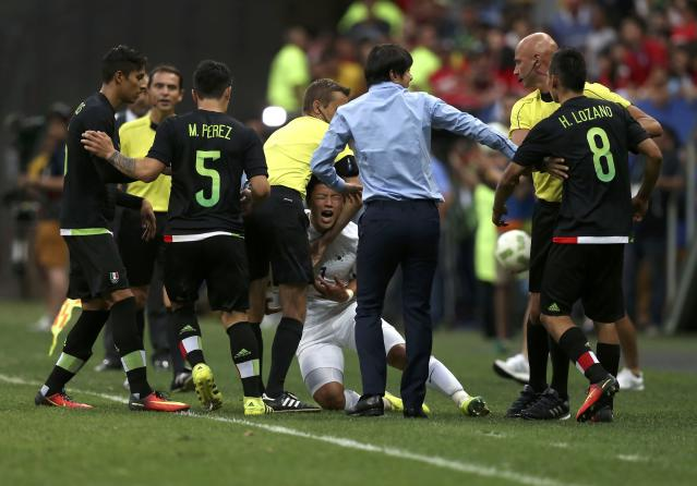 2016 Rio Olympics - Soccer - Preliminary - Men's First Round - Group C South Korea v Mexico - Mane Garrincha Stadium - Brasilia, Brazil - 10/08/2016. Referees hold apart Hirving Lozano (MEX) of Mexico from Heechan Hwang (KOR) of South Korea as they scuffle. REUTERS/Ueslei Marcelino FOR EDITORIAL USE ONLY. NOT FOR SALE FOR MARKETING OR ADVERTISING CAMPAIGNS.