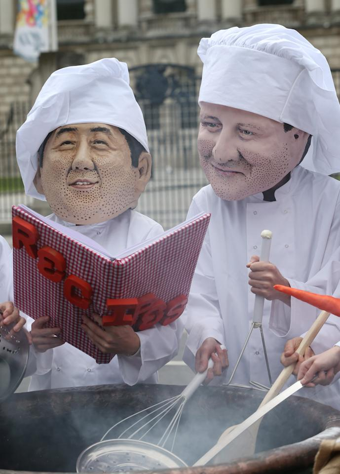 BELFAST, NORTHERN IRELAND - JUNE 16: Oxfam workers wear masks depicting Japanese Prime Minister Shinzo Abe (L) and Britain's Prime Minister David Cameron during a photocall on June 16, 2013 in Belfast, Northern Ireland. The G8 group of world leaders will meet tomorrow in Fermanagh, Northern Ireland. (Photo by Peter Macdiarmid/Getty Images)