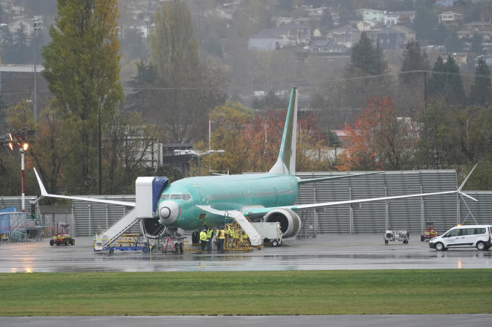Workers stand near a Boeing 737 Max airplane parked at Renton Municipal Airport, Wednesday, Nov. 18, 2020, next to the Boeing assembly facility in Renton, Wash. where 737 Max airplanes are made. After nearly two years and a pair of deadly crashes, the U.S. Federal Aviation Administration announced Wednesday that the 737 Max has been cleared for flight after regulators around the world grounded the Max in March 2019, after the crash of an Ethiopian Airlines jet. (AP Photo/Ted S. Warren)