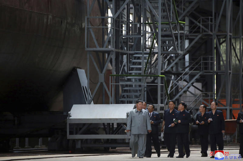 """In this undated photo provided on Tuesday, July 23, 2019, by the North Korean government, North Korean leader Kim Jong Un, left, inspects a newly built submarine to be deployed soon, at an unknown location in North Korea. North Korean state media's report on Tuesday comes days after North Korea said it may lift its 20-month suspension of nuclear and missile tests to protest expected military drills between the United States and South Korea. Independent journalists were not given access to cover the event depicted in this image distributed by the North Korean government. The content of this image is as provided and cannot be independently verified. Korean language watermark on image as provided by source reads: """"KCNA"""" which is the abbreviation for Korean Central News Agency. (Korean Central News Agency/Korea News Service via AP)"""