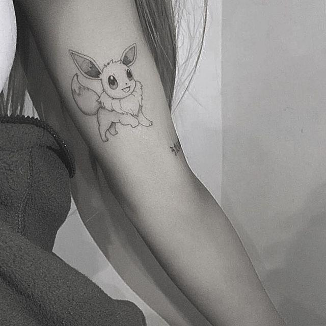 """<p>At the start of 2019, Grande added the Pokémon character Eevee to her left bicep. </p><p>The beloved animated character doesn't just evolve into one other Pokémon version but several which is perhaps why she chose it, and was added by tattoo artist Kane Navasard.</p><p><a href=""""https://www.instagram.com/p/BsoA2R9l0Ik/"""" rel=""""nofollow noopener"""" target=""""_blank"""" data-ylk=""""slk:See the original post on Instagram"""" class=""""link rapid-noclick-resp"""">See the original post on Instagram</a></p>"""