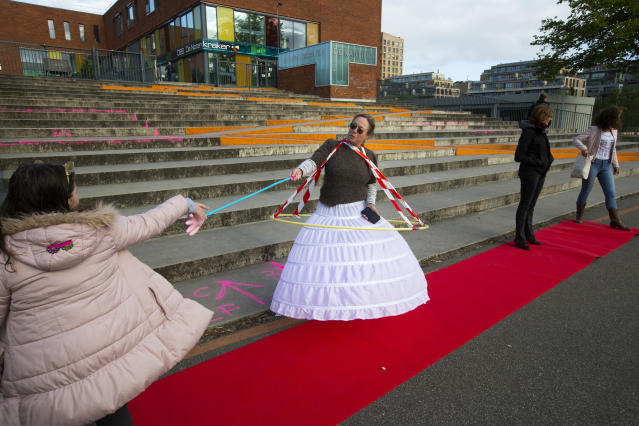 Antoinette van Zalinge, principal of the public elementary school De Notenkraker, who dressed up to show the need of social distancing, welcomes pupils in Amsterdam, Monday, May 11, 2020, as primary schools, barber shops and libraries reopened after a partial lockdown because of the outbreak of the COVID-19 coronavirus. (AP Photo/Peter Dejong)