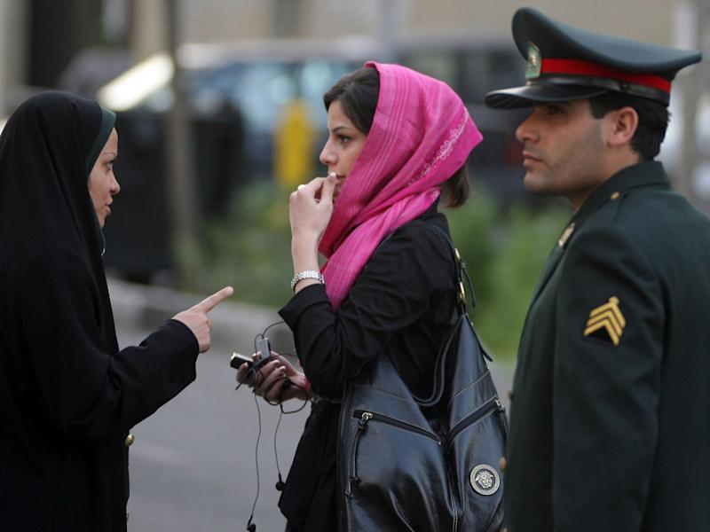 An Iranian policewoman (L) warns a woman about her clothing and hair during a crackdown to enforce Islamic dress code on April 22, 2007 in Tehran, Iran (Getty Images)
