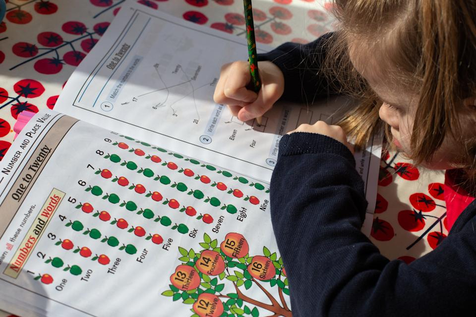 A 6-year-old girl in London fills out a maths book at her kitchen table as schools remain closed in response to the Coronavirus outbreak. Photo credit should read: Katie Collins/EMPICS
