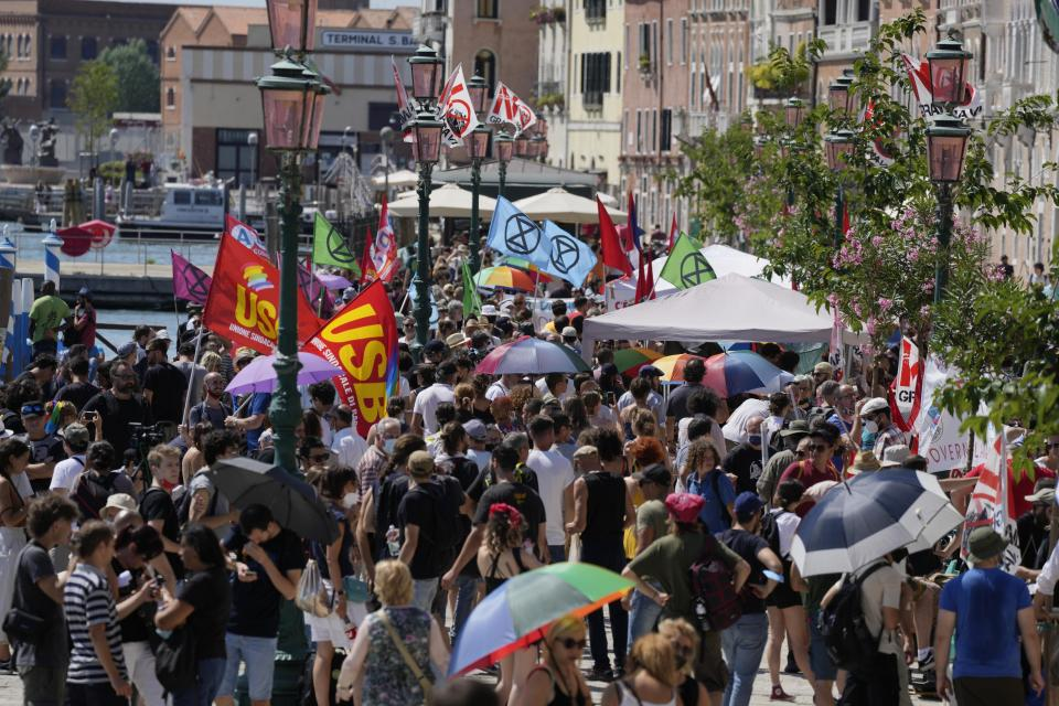 Demonstrators wave their flags as they start a protest against the G20 Economy and Finance ministers and Central bank governors' meeting in Venice, Italy, Saturday, July 10, 2021. (AP Photo/Luca Bruno)