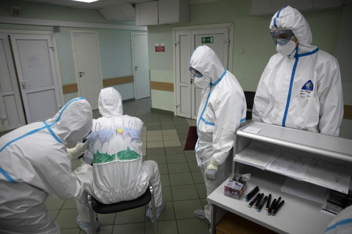 In this photo taken on Saturday, May 16, 2020, Dr. Osman Osmanov waits as a medical worker paints his protective gear during a rest on his shift at the Filatov City Clinical Hospital in Moscow, Russia. Moscow accounts for about half of all of Russia's coronavirus cases, a deluge that strains the city's hospitals and has forced Osmanov to to work every day for the past two months, sometimes for 24 hours in a row. (AP Photo/Pavel Golovkin)