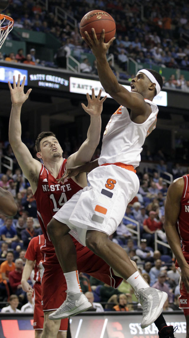 Syracuse's C.J. Fair (5) drives to the basket against North Carolina State's Jordan Vandenberg (14) during the first half of a quarterfinal NCAA college basketball game at the Atlantic Coast Conference tournament in Greensboro, N.C., Friday, March 14, 2014. (AP Photo/Bob Leverone)