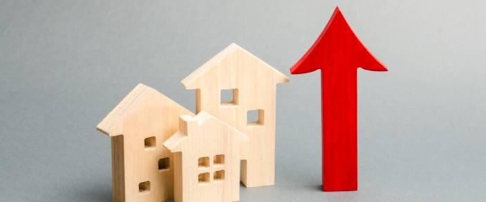 Miniature wooden houses and red arrow up. The concept of rising mortgage rates.
