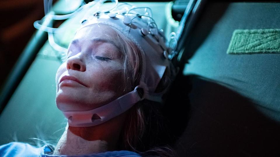 Nathalie Boltt lies with her eyes closed, her head in some kind of brain monitoring device, in Demonic