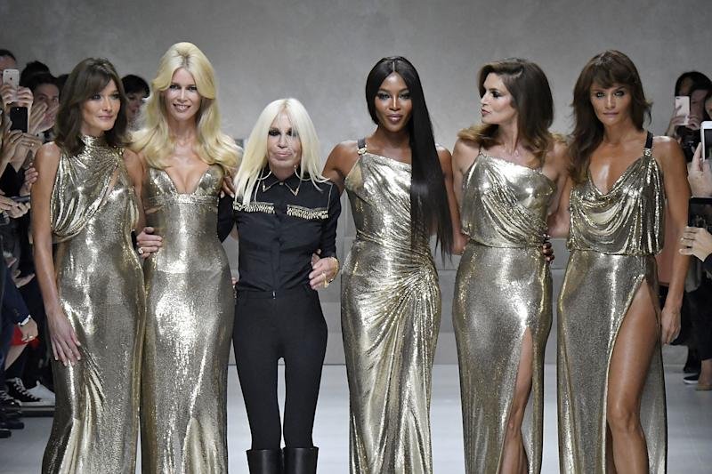Naomi Campbell reuniting with fellow supermodels Carla Bruni, Claudia Schiffer, Cindy Crawford, and Helena Christensen to walk the runway of the Versace spring/summer 2018 show with Donatella Versace during Milan Fashion Week in 2017. Photo courtesy of Getty Images.