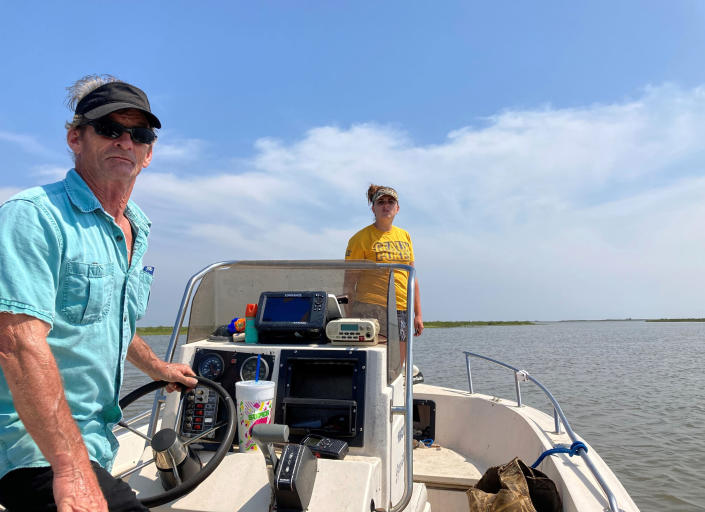 Mike Asher, left, and Chelsea Coleman, right, assist Thursday, April 29, 2021, in the search for survivors who were aboard the Seacor Power, a lift boat that capsized on April 13 off the Louisiana coast. Volunteers have been searching by air and boat for any sign of those still missing. (AP Photo/Rebecca Santana)