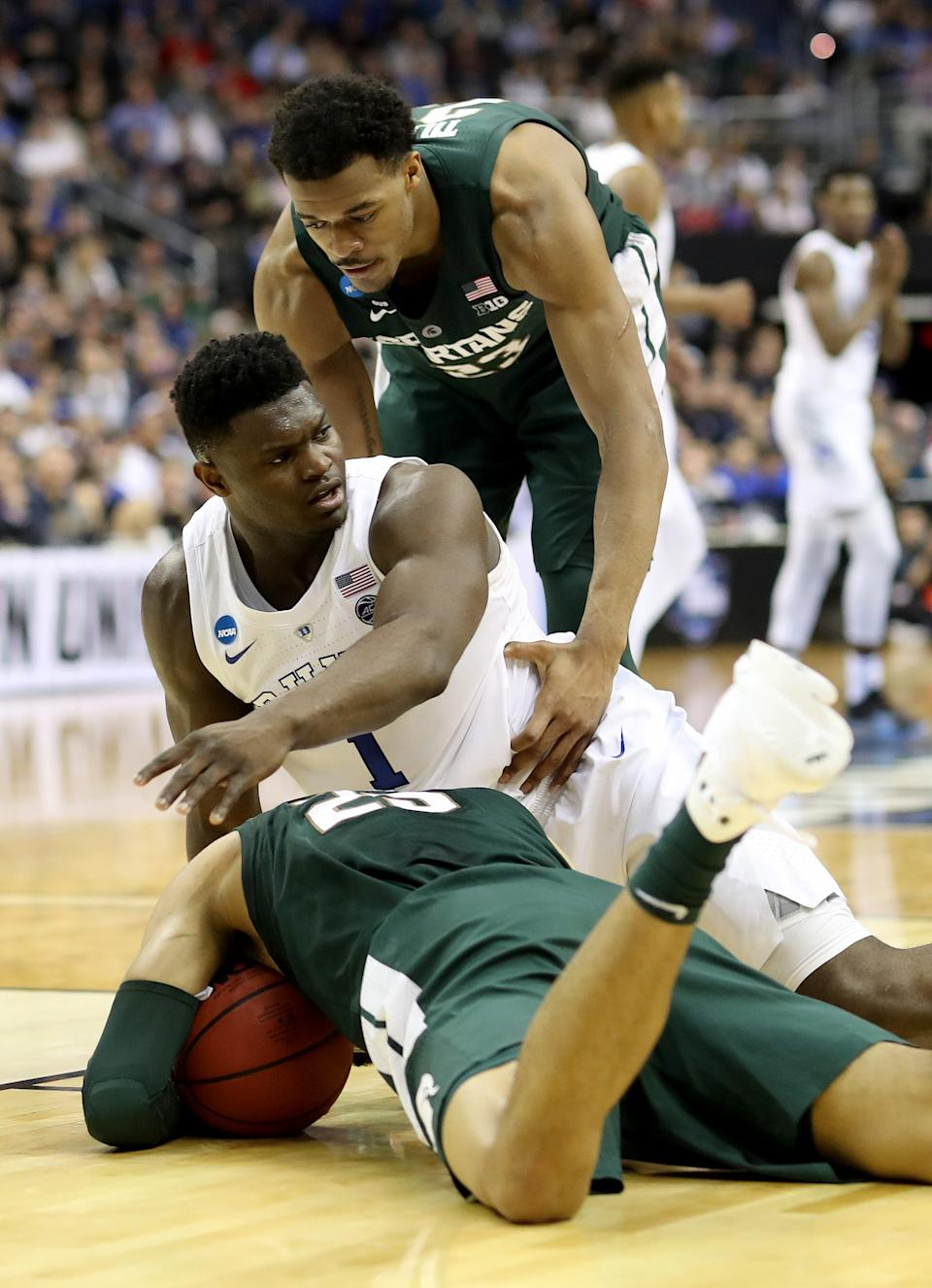 Duke's Zion Williamson reacts from the ground against Michigan State's Xavier Tillman, top, and Kenny Goins during the first half of the NCAA tournament East Region final on Sunday, March 31, 2019 in Washington.
