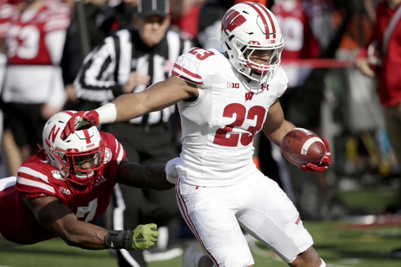 Wisconsin running back Jonathan Taylor (23) carries the ball away from Nebraska linebacker Mohamed Barry, left, during the first half of an NCAA college football game in Lincoln, Neb., Saturday, Nov. 16, 2019. (AP Photo/Nati Harnik)