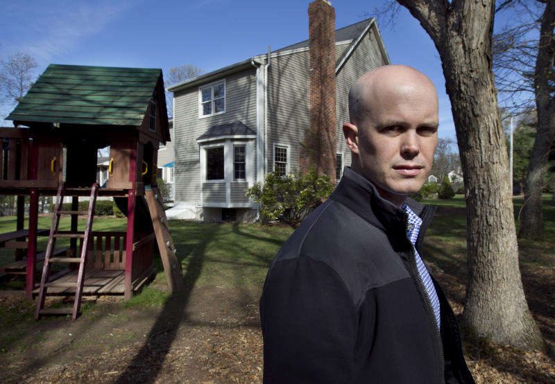 In this April 19, 2012, photo, Mike McCarthy stands in front of his home in Walpole, Mass. McCarthy's property in Walpole, and the Walpole town line are about 15 feet from the fence, and McCarthy, who has two young children, worries about the impact a casino would have so close to his home.  (AP Photo/Steven Senne)