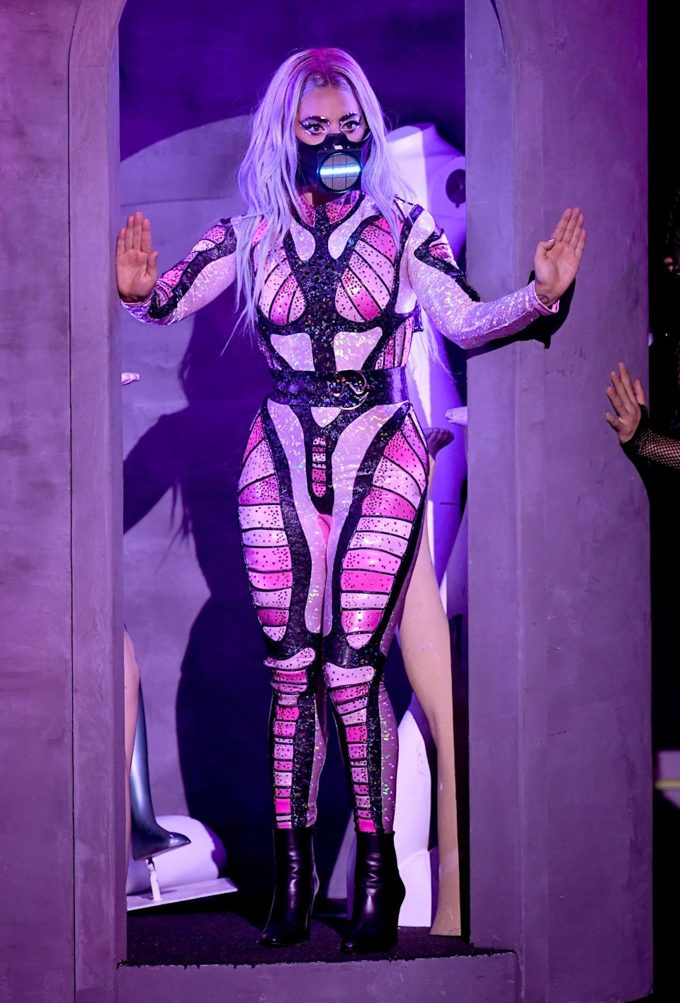 """For her third and final performance of the night, Gaga put on her first of two catsuits, this one by BCALLA. With it, she wore another digital face mask by Smooth Technology, created in collaboration with visual artist Diego Montoya. <br><br><em>Lady Gaga is wearing a BCALLA catsuit, Saint Laurent shoes, and a Smooth Technology x Diego Montoya digital mask.</em><br><br><br><br><br><br><span class=""""copyright"""">Photo: Kevin Winter/Getty Images.</span>"""