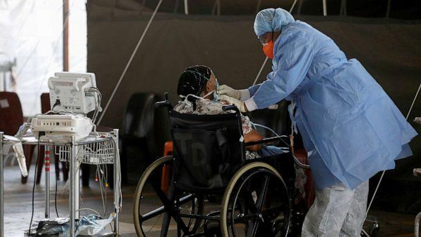 PHOTO: A healthcare worker tends to a patient at a temporary ward set up during the coronavirus disease (COVID-19) outbreak, at Steve Biko Academic Hospital in Pretoria, South Africa, Jan. 19, 2021. (Phill Magakoe/Pool via Reuters/FILE)