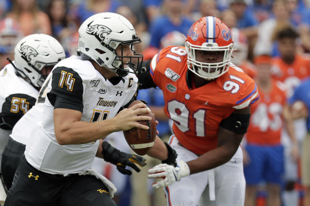 Towson quarterback Tom Flacco (14) scrambles from the pocket as he is pressured by Florida defensive lineman Marlon Dunlap Jr. (91) during the first half of an NCAA college football game, Saturday, Sept. 28, 2019, in Gainesville, Fla. (AP Photo/John Raoux)