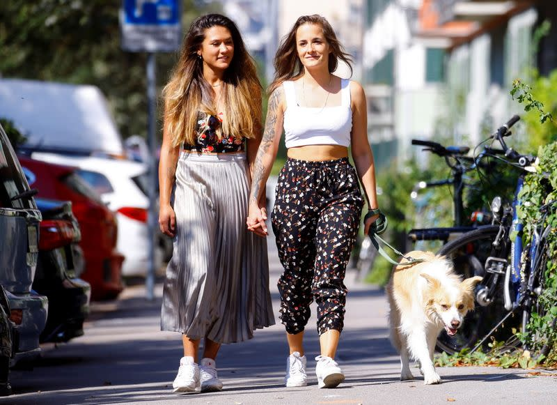Young lesbian couple walk with their border collie dog Ted in Zurich
