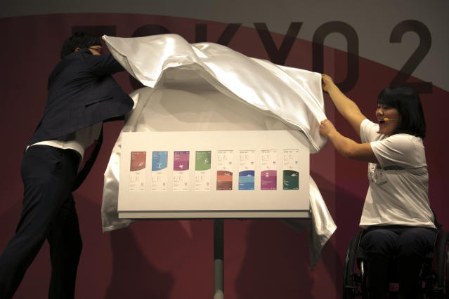Paralympian Monika Seryu, right, and comedian Ryota Yamasato unveil tickets for the Tokyo 2020 Olympics and Paralympics Wednesday, Jan. 15, 2020, in Tokyo. (AP Photo/Jae C. Hong)