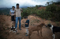 Nery Flores, 22, and his wife, Ada Castron, 19, stand with their son, Daniel Flores, 3, at the site of their home destroyed by a landslide triggered by hurricanes Eta and Iota in the village of La Reina, Honduras, Saturday, June 26, 2021. No one died. But seven months later, La Reina's people remain homeless, and adrift. (AP Photo/Rodrigo Abd)