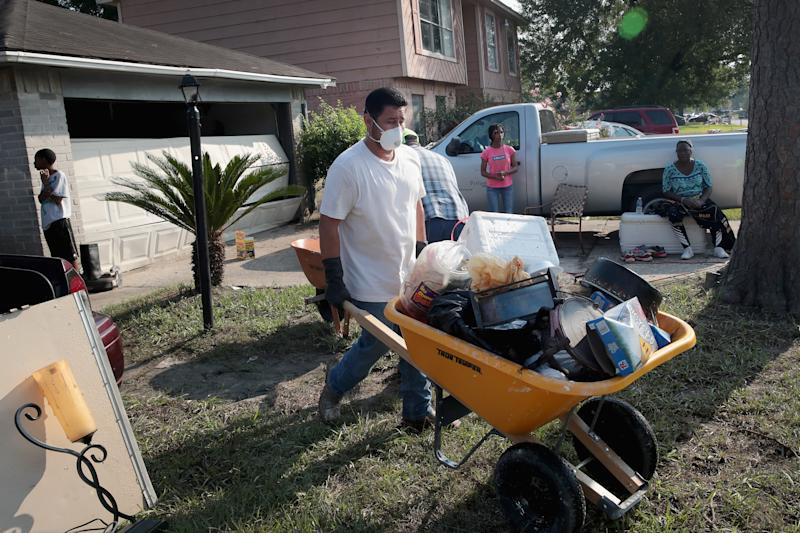 Volunteers from Performance Contractors help a co-worker clean up the damage to his Houston home after Harvey. (Scott Olson via Getty Images)