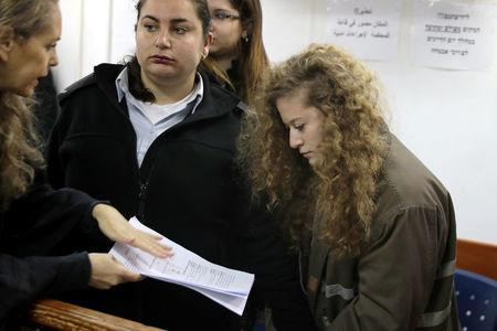 Palestinian teen Ahed Tamimi (R) looks at a document handed to her by lawyer Gaby Lasky at the military courtroom at Ofer Prison, near the West Bank city of Ramallah, February 13, 2018. REUTERS/Ammar Awad