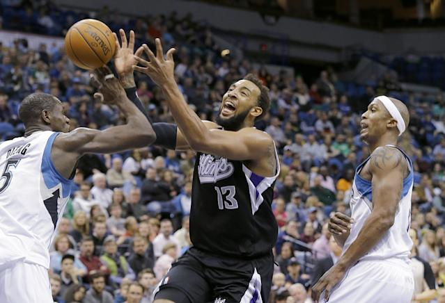 Minnesota Timberwolves center Gorgui Dieng, left, strips the ball from Sacramento Kings forward Derrick Williams (13) as Williams drives to the basket between Dieng and Timberwolves forward Dante Cunningham, right, during the second quarter of an NBA basketball game in Minneapolis, Sunday, March 16, 2014. (AP Photo/Ann Heisenfelt)