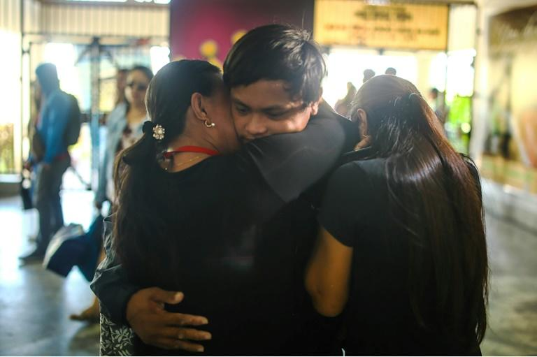Filipino fisherman Rolando Omongos (C) 21 is hugged by his mother Rosalie (L) and another sibling, shortly after arriving at General Santos City airport