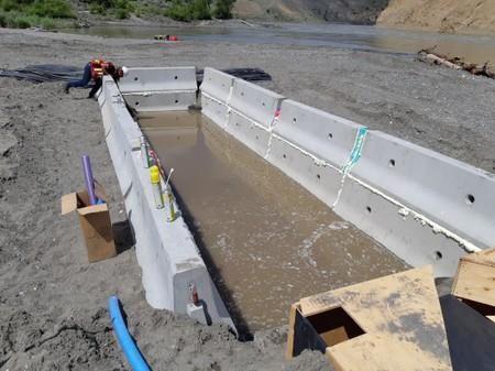 A trench to be used as a holding pond for migrating salmon is constructed near the Big Bar landslide