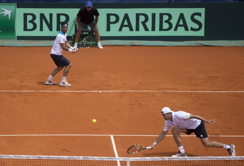 Italy's Simone Bolelli, right, returns the ball to Argentina's doubles team Horacio Zeballos and Eduardo Schwank as his teammate Fabio Fognini look on at left during their Davis Cup doubles match in Mar del Plata, Argentina, Saturday, Feb. 1, 2014. (AP Photo/Eduardo Di Baia)