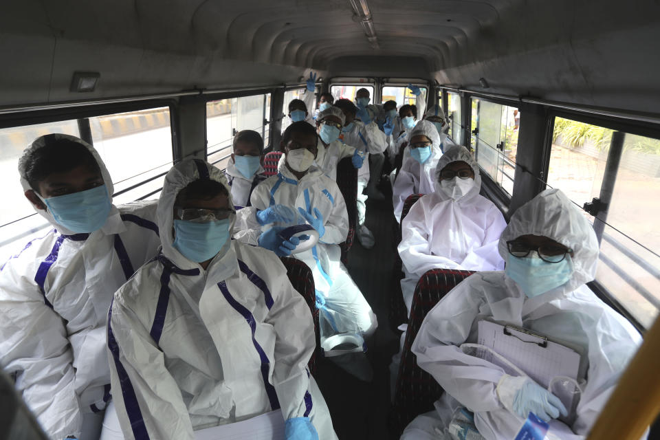 """Health workers arrive on a bus to conduct a free medical checkup at residential building in Mumbai, India, Thursday, July 2, 2020. Indian Prime Minister Narendra Modi said in a live address Tuesday that the country's coronavirus death rate is under control, but that the country is at a """"critical juncture."""" But since the lockdown was lifted, the caseload has shot up, making India the world's fourth-worst affected country. (AP Photo/Rafiq Maqbool)"""