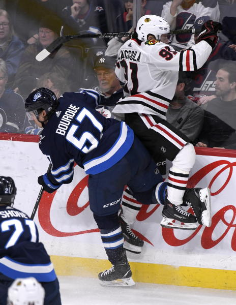 Winnipeg Jets' Gabriel Bourque (57) checks Chicago Blackhawks' Drake Caggiula (91) during the third period of an NHL hockey game Sunday, Feb. 16, 2020, in Winnipeg, Manitoba. (Fred Greenslade/The Canadian Press via AP)