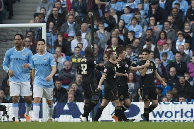 Wigan's Jordi Gomez, right, celebrates with teammates after scoring a penalty against Manchester City during their English FA Cup quarterfinal soccer match at the Etihad Stadium, Manchester, England, Sunday, March 9, 2014. (AP Photo/Jon Super)