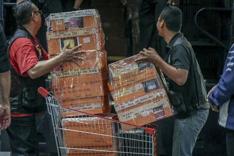 Investigators lift sealed boxes believed to contain luxury designer bags into a Black Maria outside the Pavilion Residences condominium in Kuala Lumpur. May 18, 2018. — Picture by Hari Anggara
